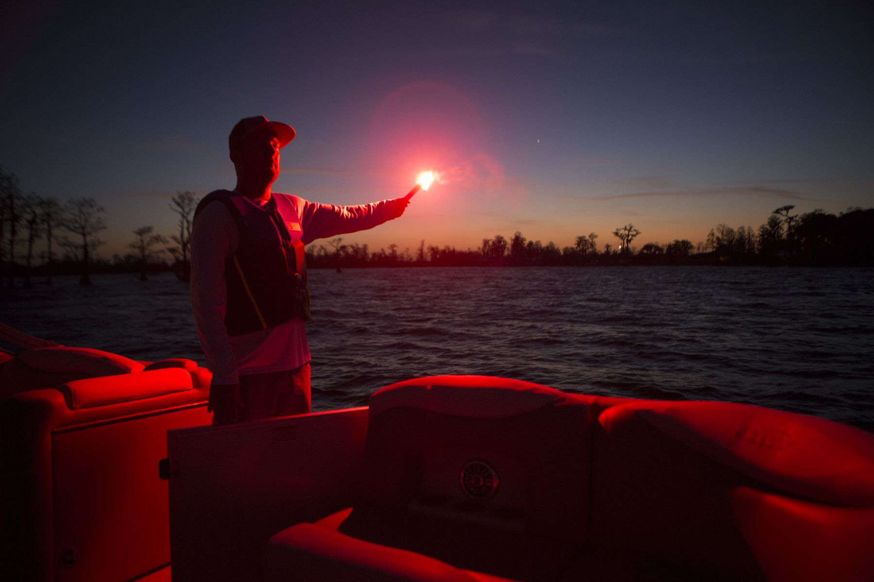 Using a handheld flare at dusk aboard a boat 16-21 feet.