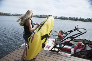 Kids loading the boat for a fun afternoon on the water in properly fitting life jackets.