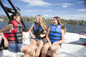 Kids having a fun afternoon on the water in properly fitting life jackets.