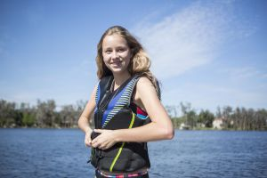A girl zipping a life jacket for a day on the water.