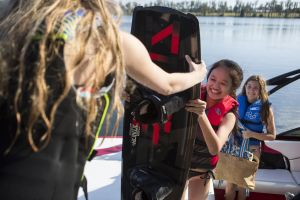 Kids unloading the boat after a day having fun on the water in properly fitting life jackets.