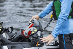 Using a safety lanyard kill switch on a personal watercraft while wearing a properly fitting life jacket.