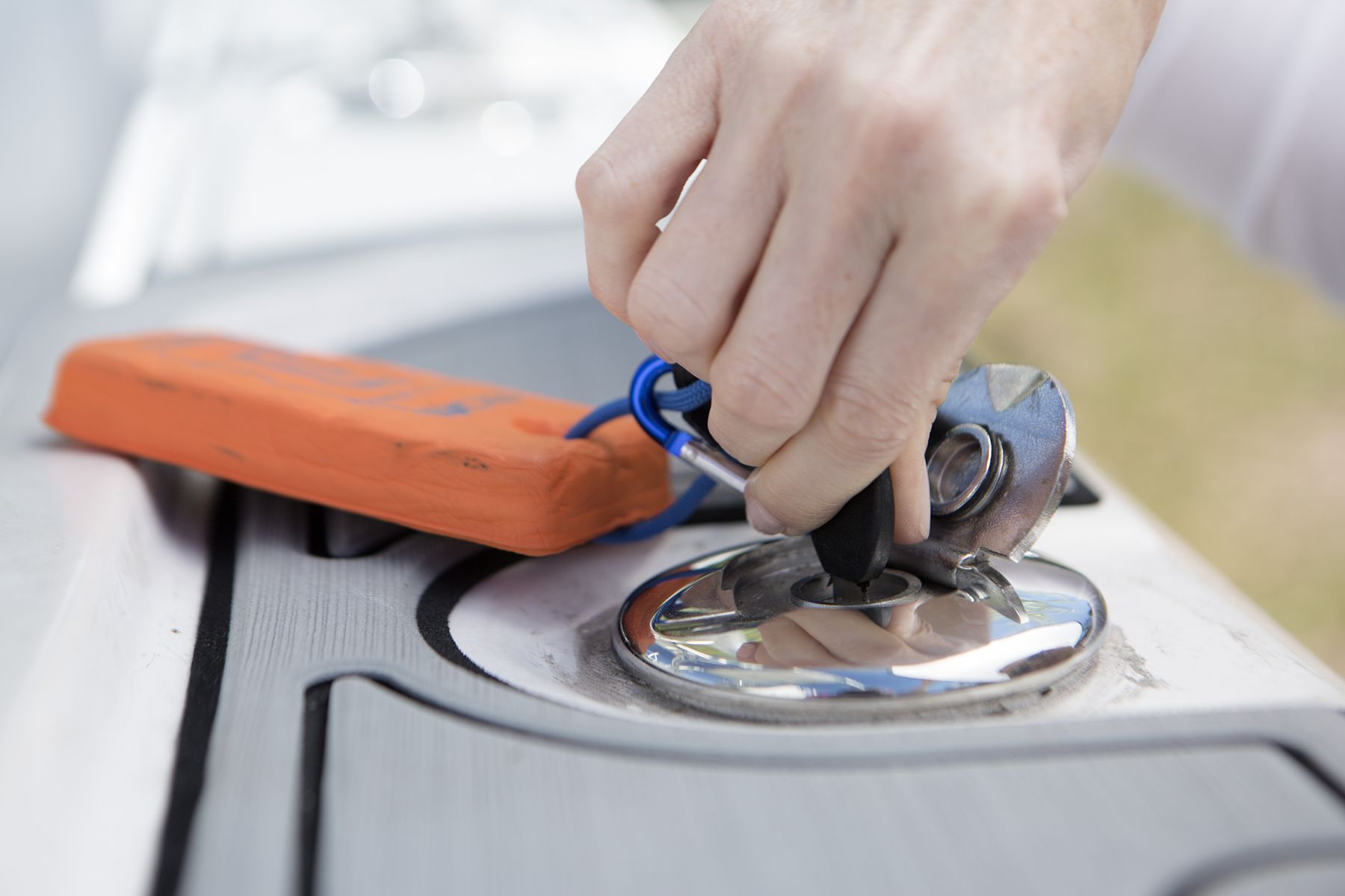 Opening a locked gas cap on a boat.