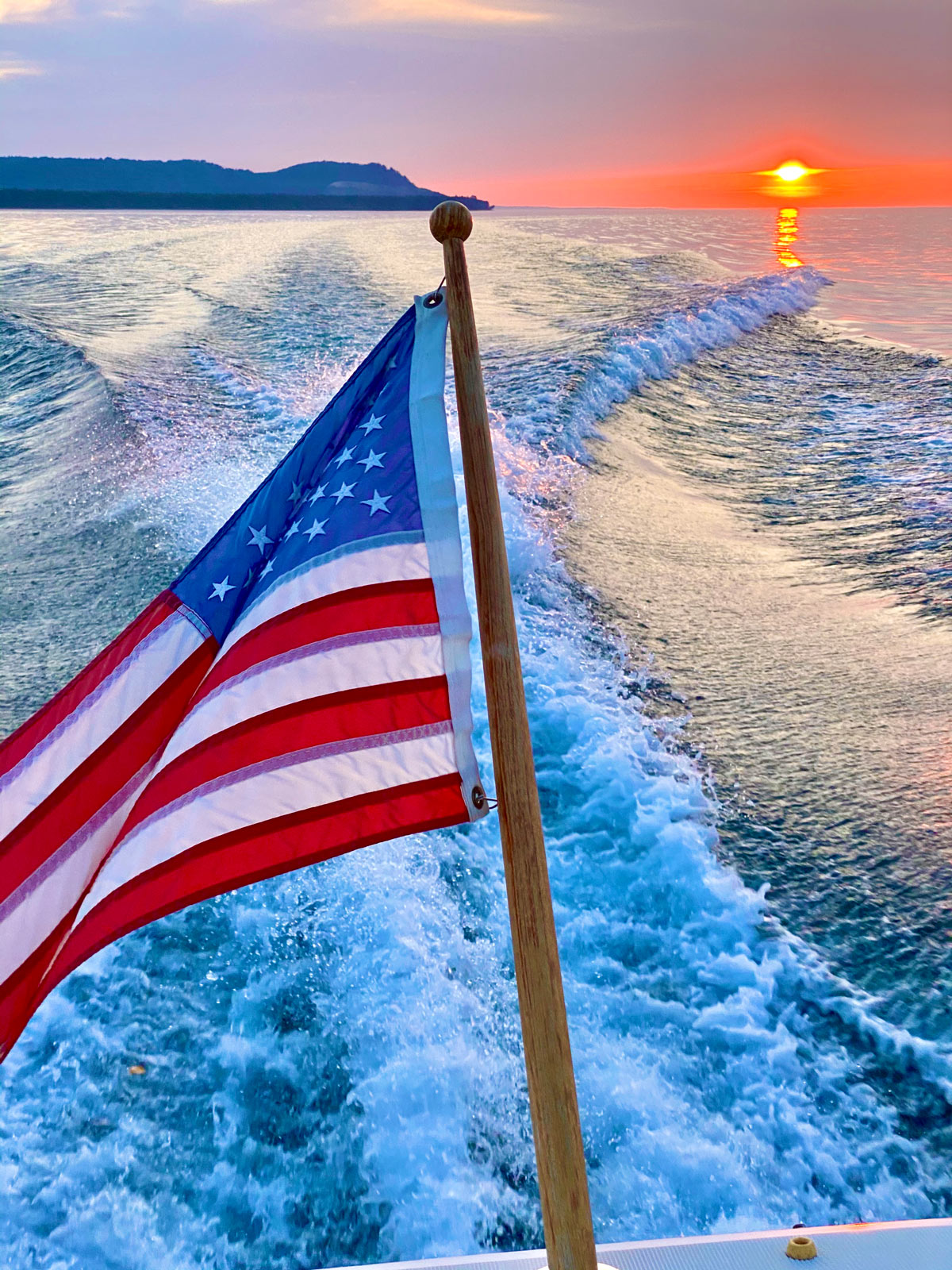 An American flag at the back of a moving boat, with a beautiful sunset in the background.